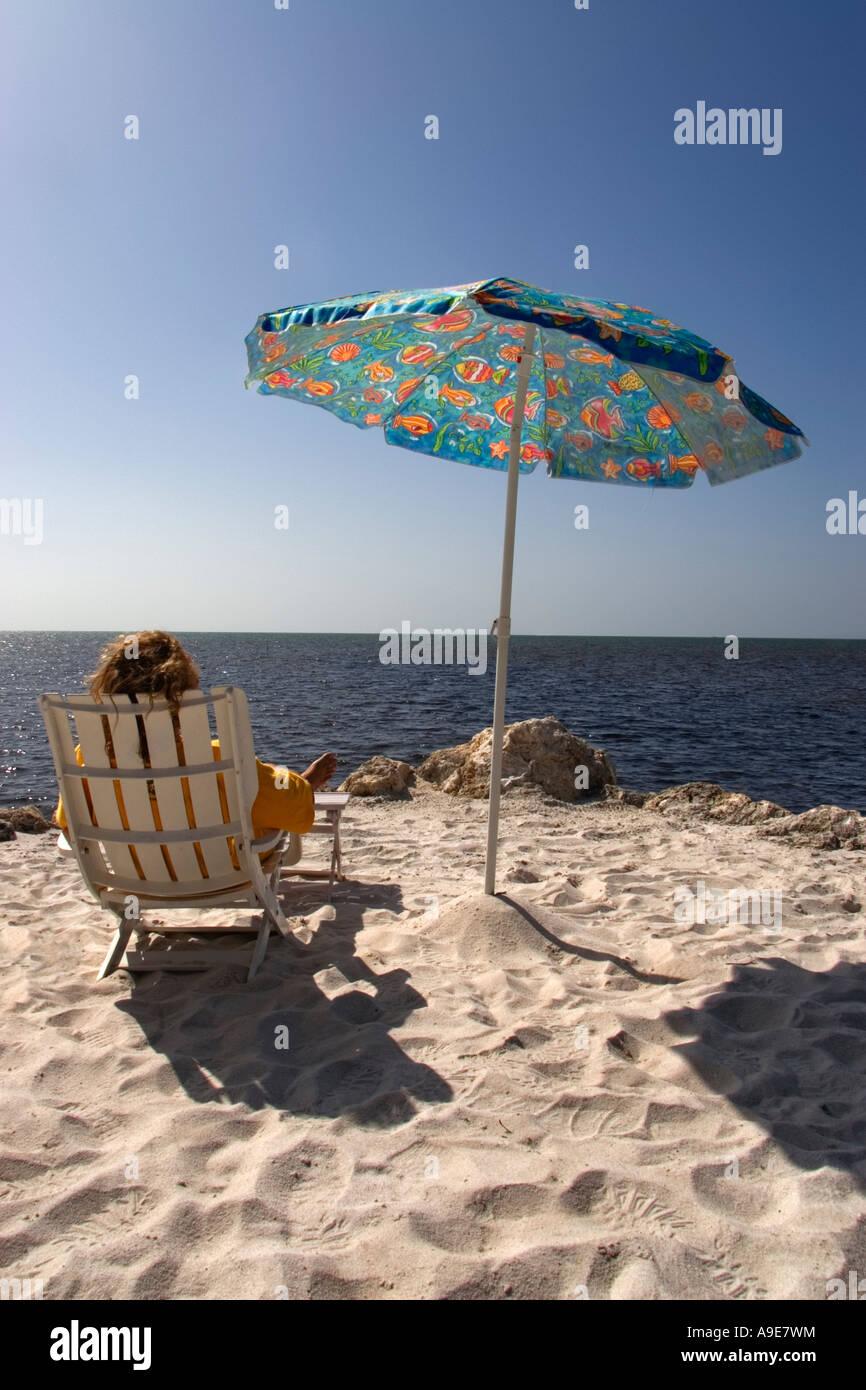 https www alamyimages fr photo image vue arriere d une personne assise sur une chaise de plage dans un cadre face a la mer 12339679 html