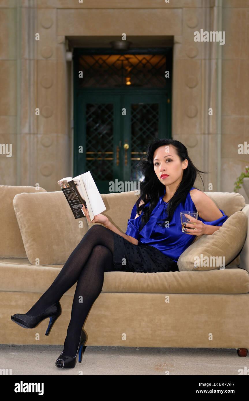 jolie femme asiatique avec jambes croisees sur un canape sur une terrasse exterieure avec un verre et une reservation dans un hotel particulier de l usine