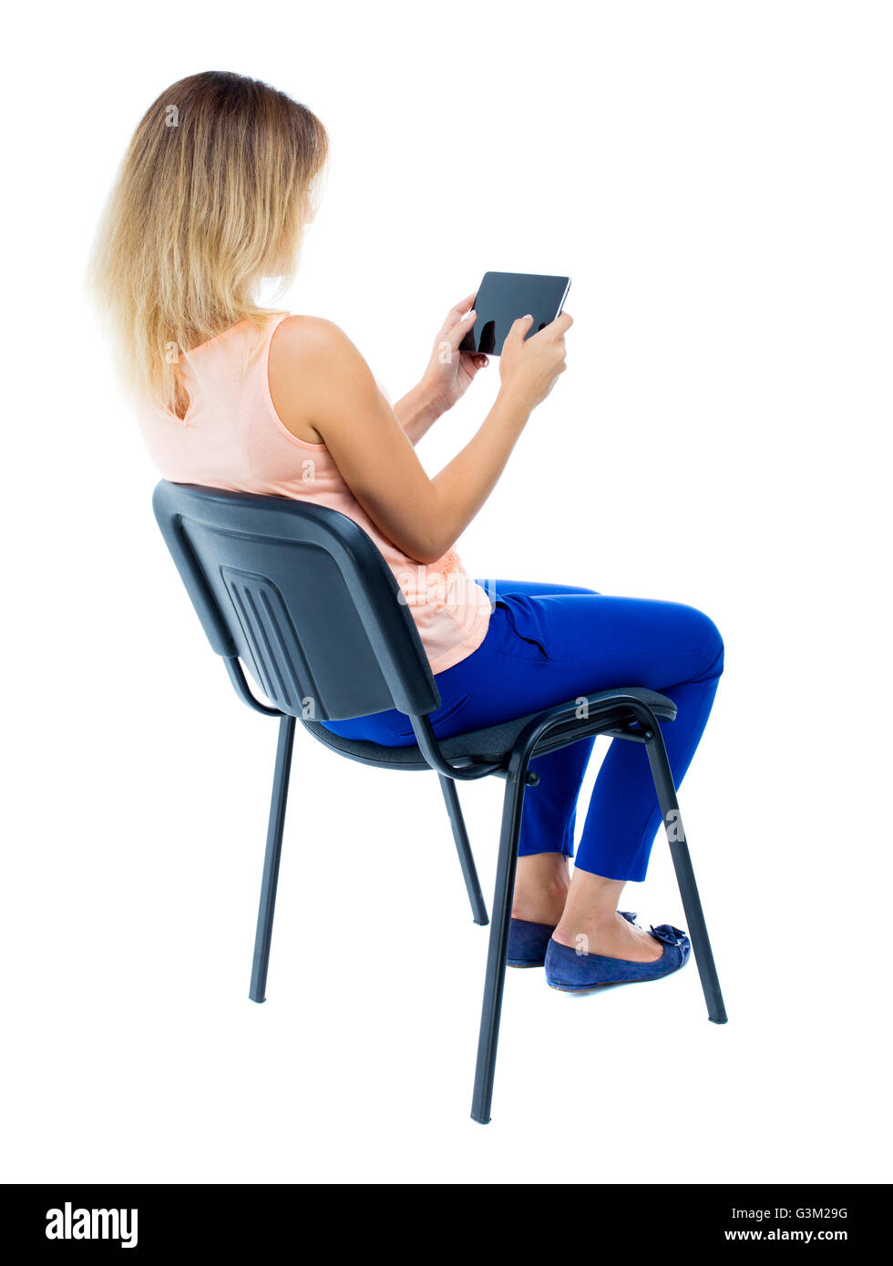 https www alamyimages fr photo image vue arriere de femme assise sur une chaise et regarde l ecran de la tablette vue arriere vue arriere collection les gens de personne plus isole sur fond blanc blonde en pantalon bleu assis de cote sur la chaise de bureau et joue le jeu 105547052 html