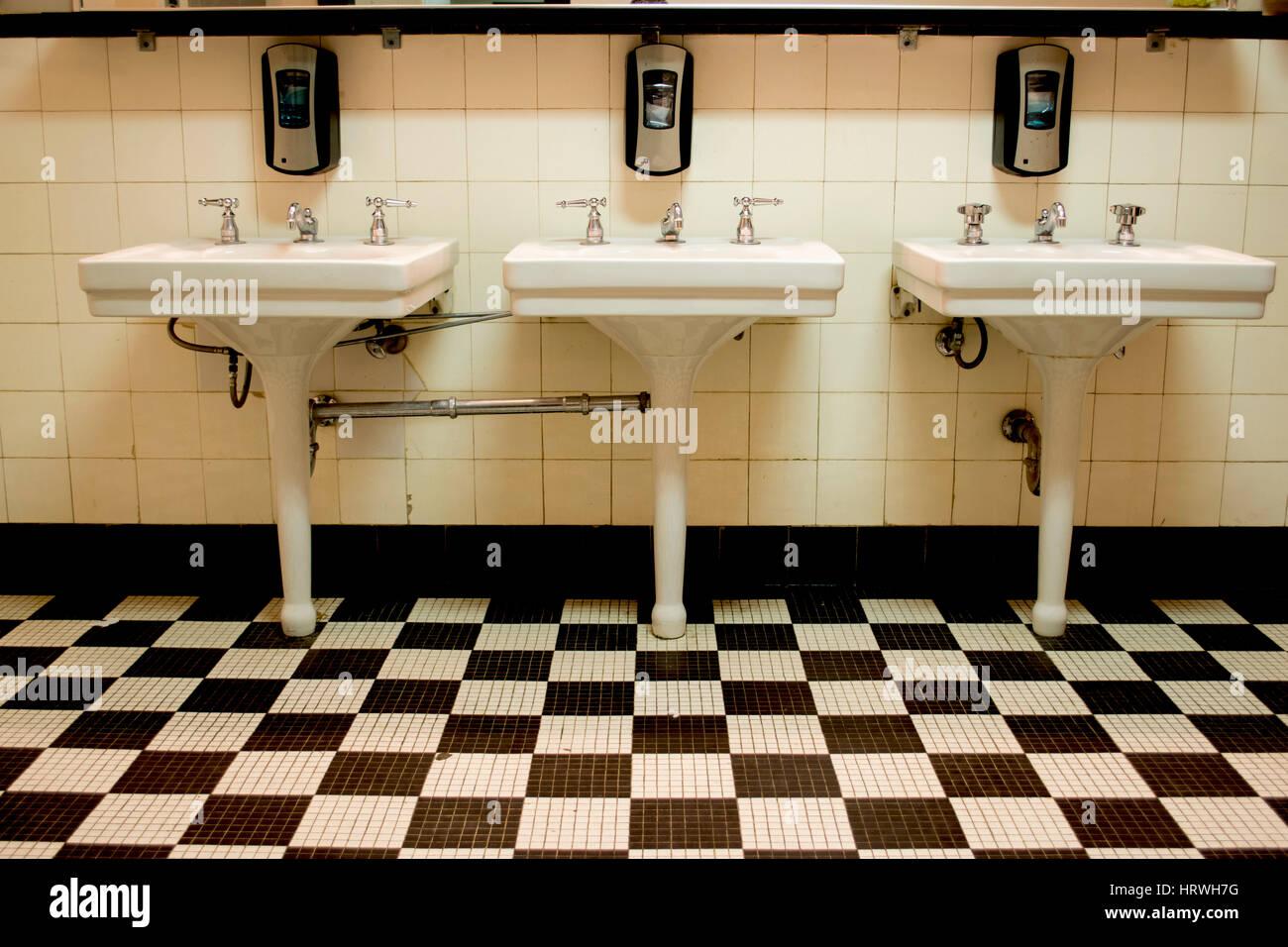 https www alamyimages fr photo image trois puits de porcelaine blanche dans une vieille salle de bains publics art deco avec un carrelage en damier noir et blanc marbre 135172004 html