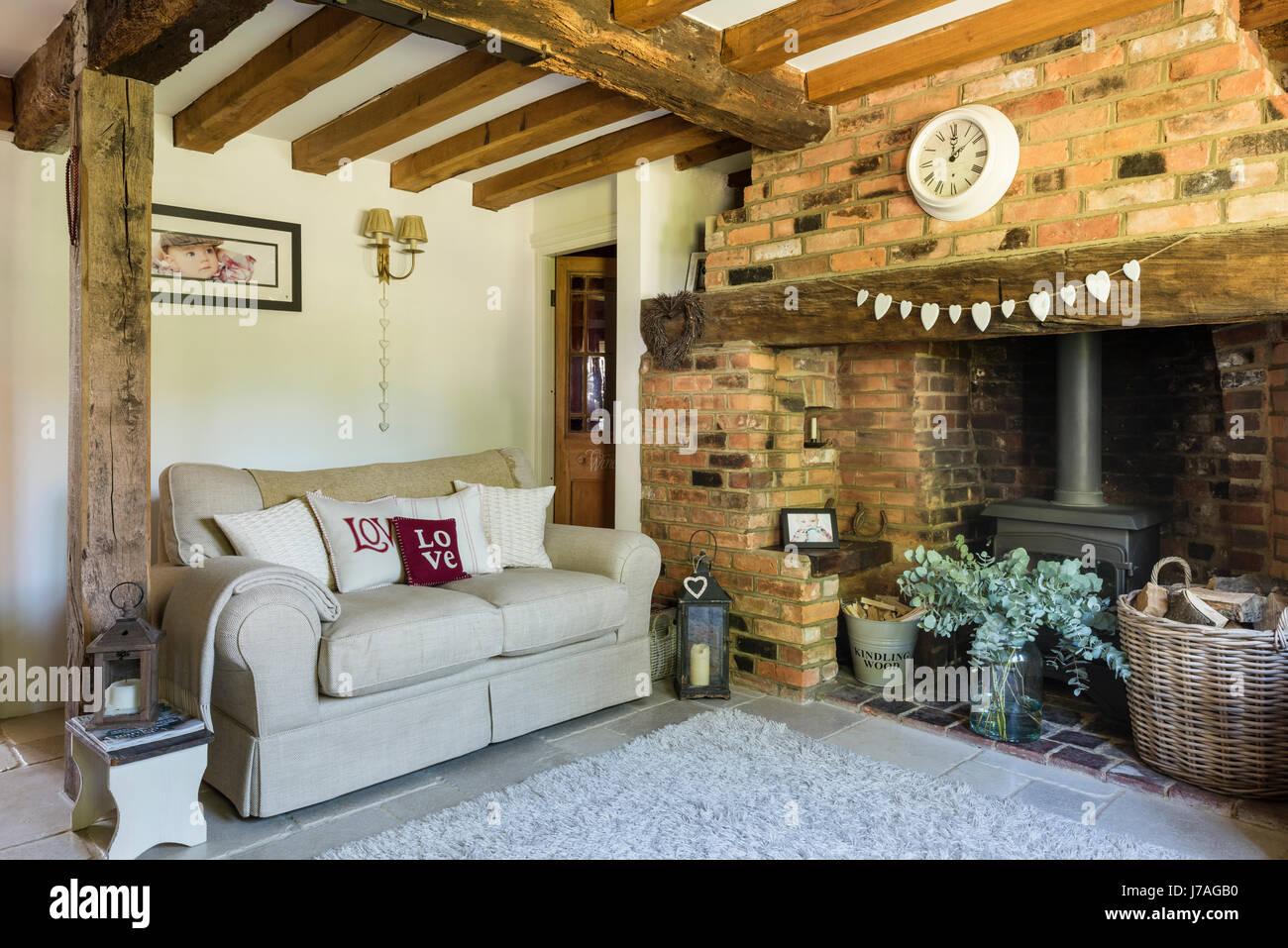 https www alamyimages fr photo image confortable salon avec cheminee mur en briques apparentes et de poutres apparentes au plafond la creme canape est de laura ashley et le tapis de john lewi 142217908 html