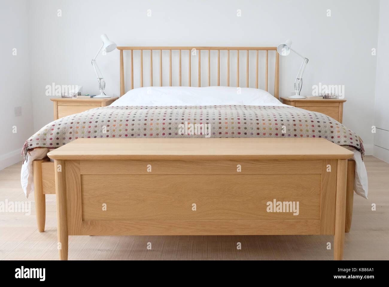 chambre d inspiration scandinave montrant l interieur meubles de chambre a coucher en bois murs peints en blanc des draps blancs et une couverture coloree