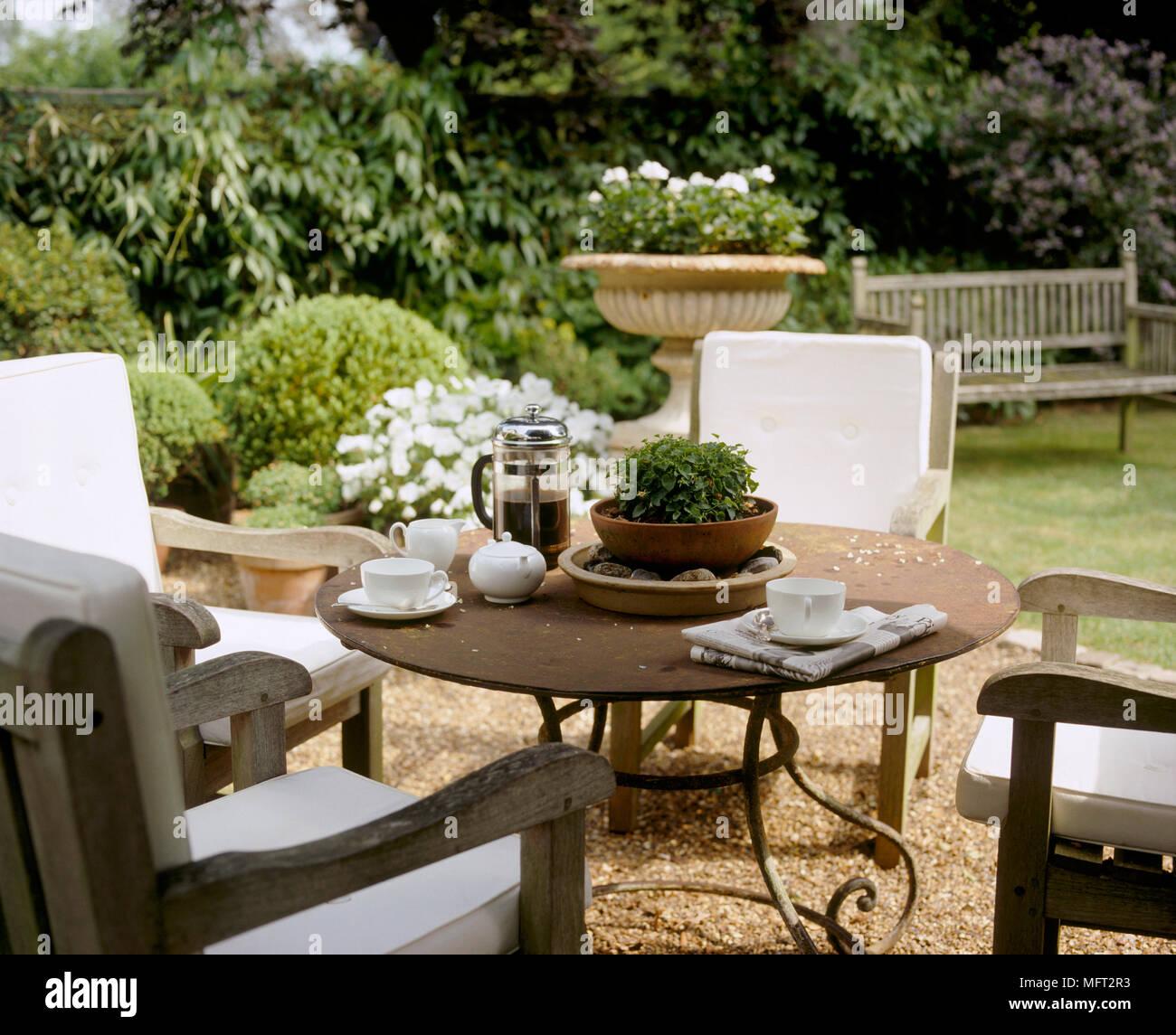 un detail d un pays jardin avec une terrasse couverte table et chaises en bois set de table pour le cafe du matin