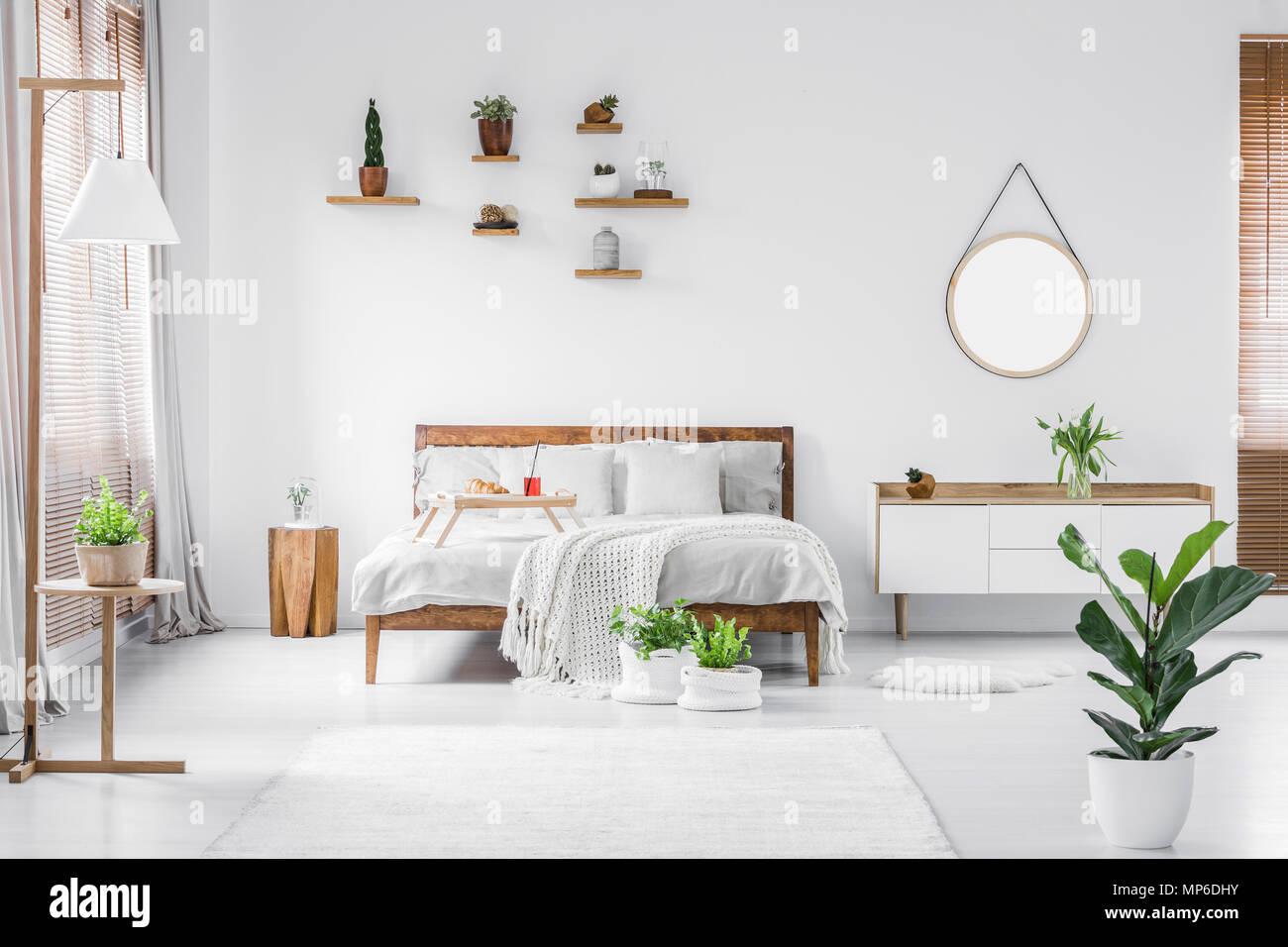 matin dans un cadre lumineux et ensoleille de l interieur chambre a coucher moderne blanc avec des meubles en bois coussins couverture et bac alimentaire