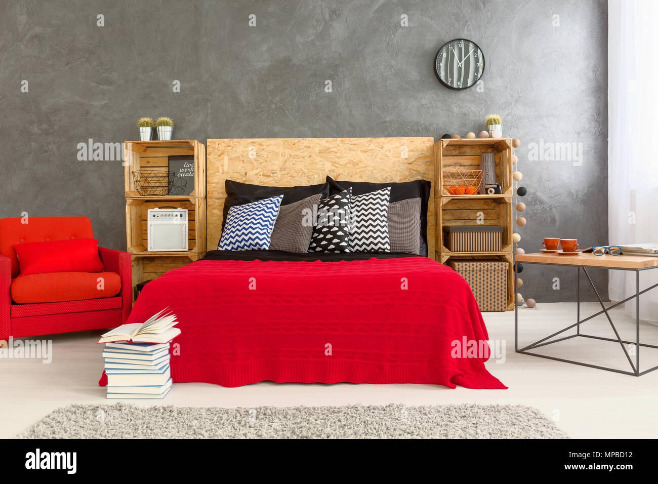 https www alamyimages fr chambre au design moderne avec lit et fauteuil rouge sur le mur gris de fond etageres en bois faite de boites en bois et tete de lit en bois pour le lit image185877806 html