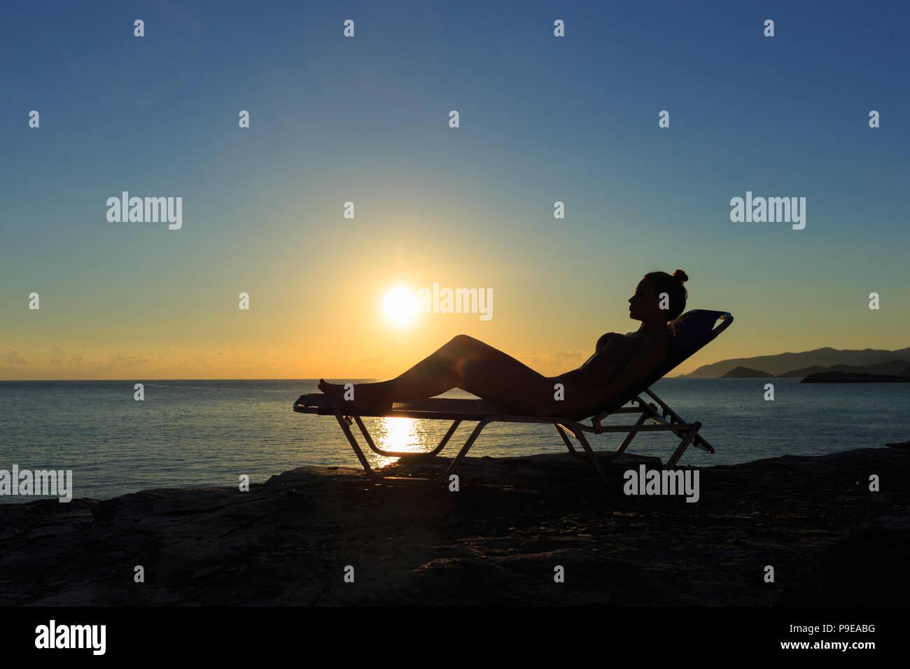 https www alamyimages fr silhouette de la jeune femme est allongee sur le transat au coucher du soleil image212371812 html