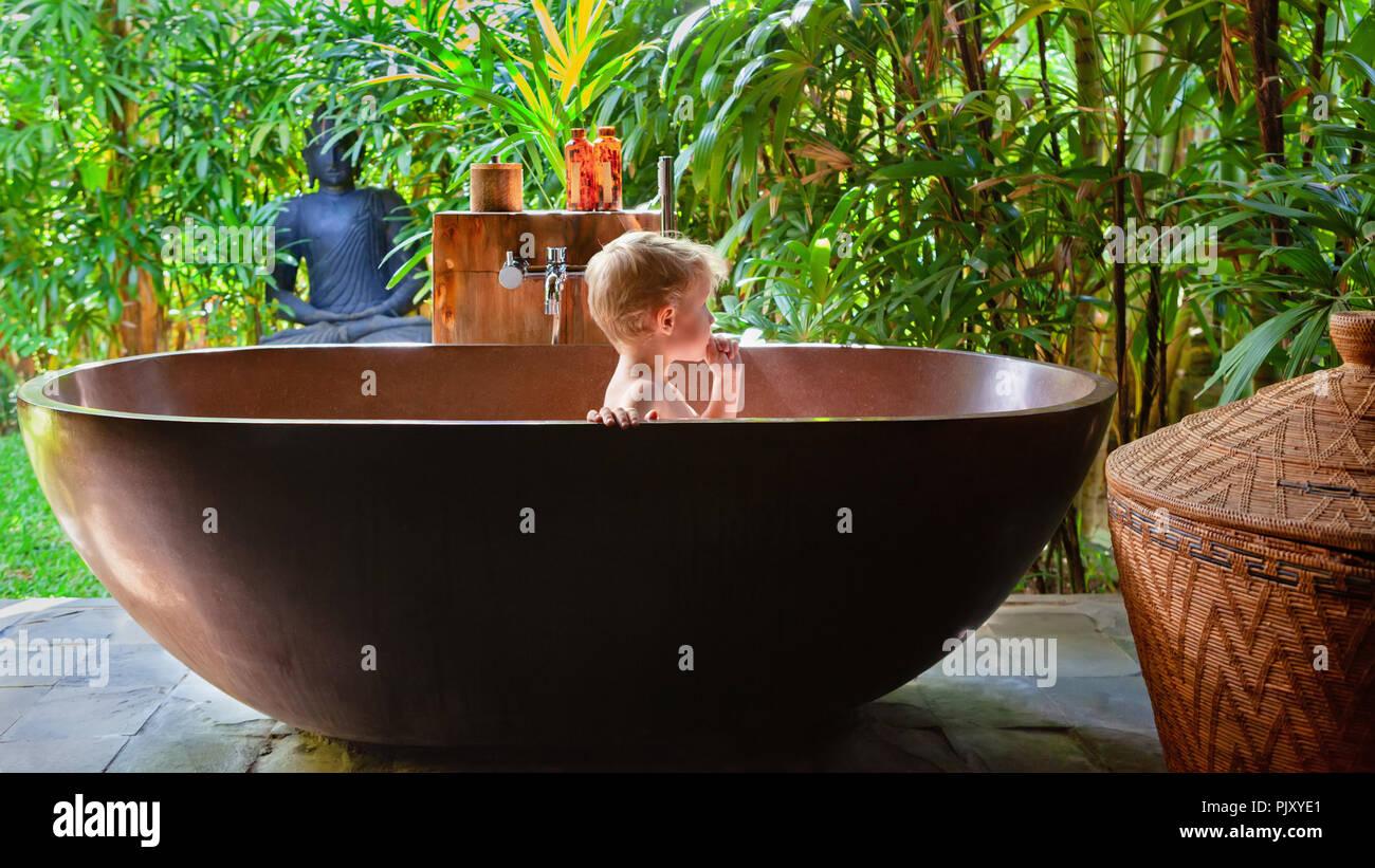 https www alamyimages fr happy baby boy s amuser dans la baignoire enfant joyeux prendre bain dans l exterieur de la salle de bains sur veranda ouverte avec belle vue sur le jardin tropical image218180537 html