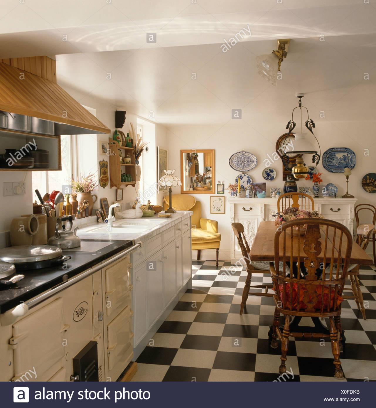 https www alamyimages fr damier noir et blanc revetement en vinyle en pays blanc d une cuisine avec table en bois et chaises windsor et aga creme image275705903 html