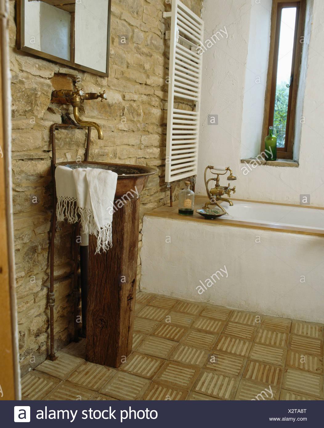 https www alamyimages fr vasque en cuivre sur socle en grange amenagee salle de bains avec mur en pierres apparentes et carrelage carriere image277130136 html