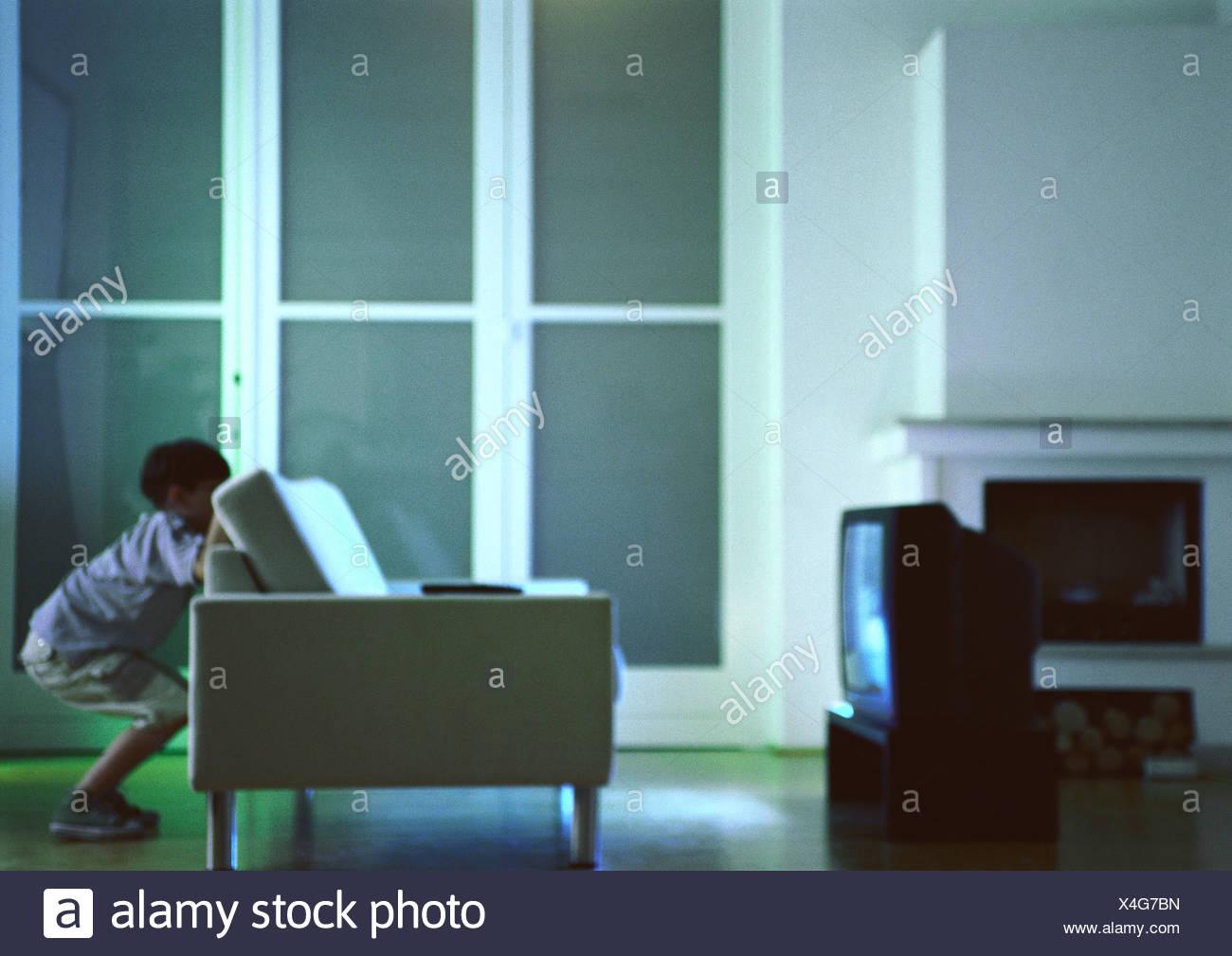 petit garcon de se cacher derriere un canape peering over oreillers a la television vue laterale