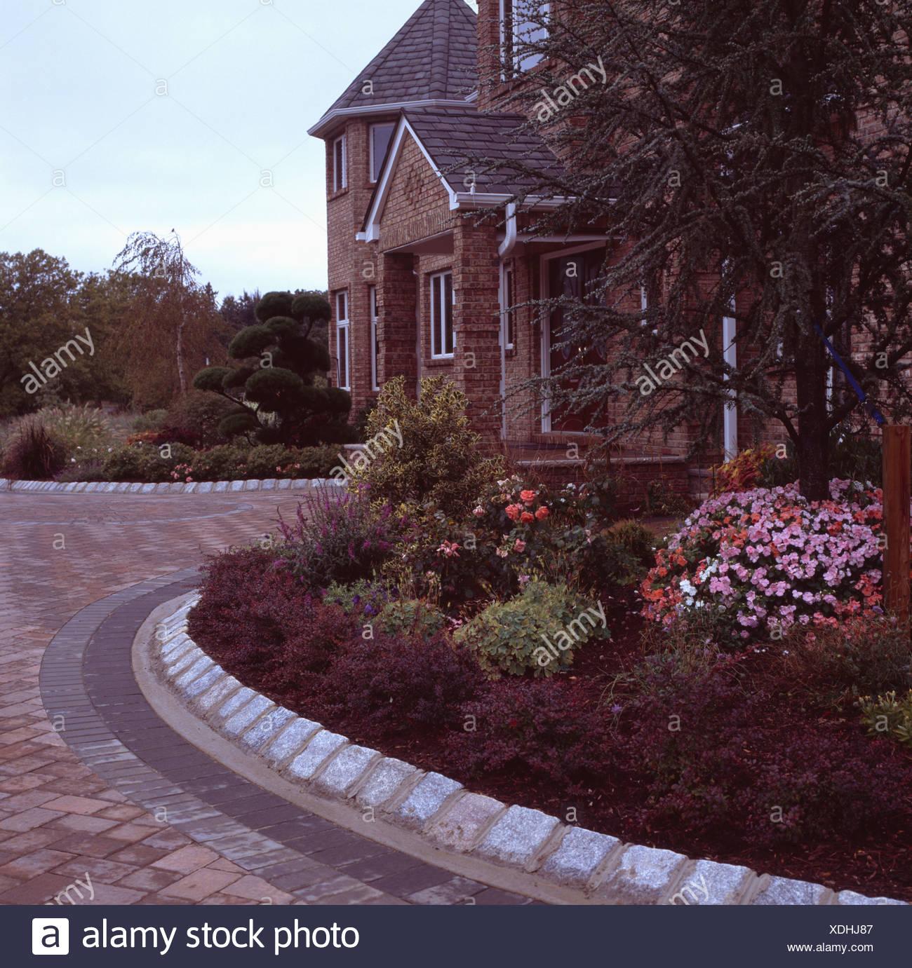https www alamyimages fr bordures de pierre autour de la frontiere de jardin en face de nouvelle construction traditionnelle maison en debut de soiree image283743943 html