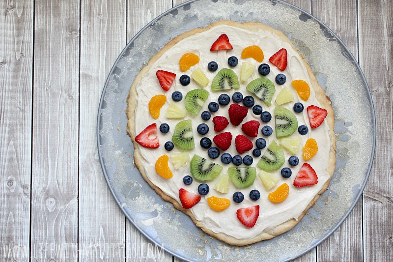 This fruit pizza is so easy and so yummy! The best way to eat fruit! A layer of soft sugar cookie, topped with cream cheese frosting, and colorful fruit! The perfect dessert for your next party!