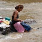 Mujer lavando ropa en un río
