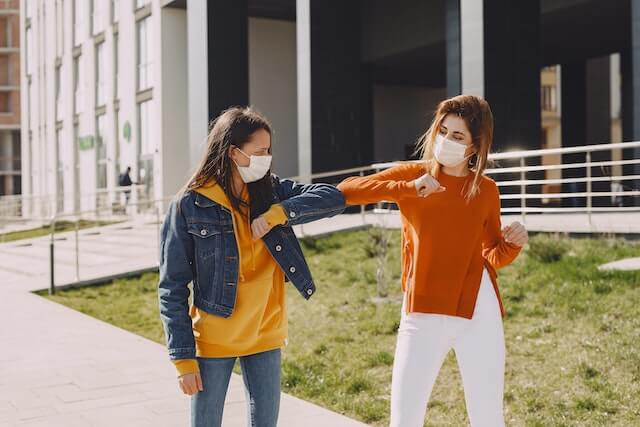 Two women with masks bumping elbows