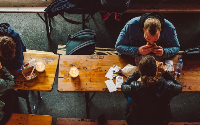 Overhead-view-of-people-eating-at-wooden-tables-outside