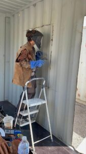 Photo of John's son at work on a container home