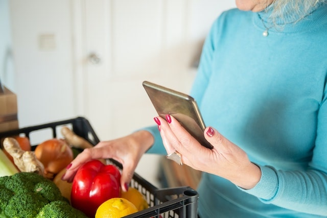 Woman holding mobile phone and going through her grocery delivery