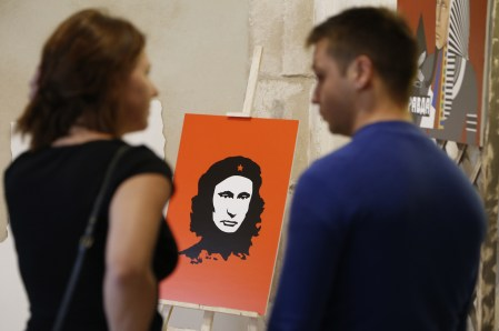 epa04965879 Journalists speak in front of an artwork depicting Russian President Vladimir Putin as Cuban Revolution legend Ernesto 'Che' Guevara (C) during the 'Putin Universe' exhibition in Moscow, Russia, 06 October 2015. Moscow and London on 06-07 October host a 'Putin Universe' exhibition organized by international group of Putin's supporters and dedicated to the Russian president's 63rd birthday. The exhibition presents Russian President Vladimir Putin as characters and heroes from various countries and eras. EPA/MAXIM SHIPENKOV