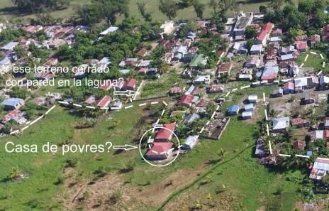 En la foto, se ve un terreno en la laguna cerrado con pared y una casa millonaria