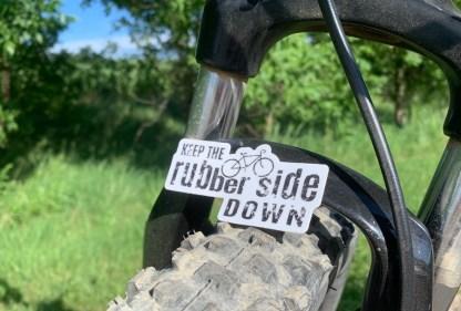 Keep the Rubber Side Down sticker on a bike wheel