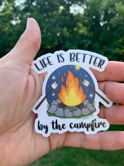 "hand holding a sticker that reads ""life is better by the campfire"""