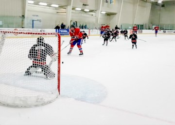 Jen Walden takes a shot against her daughter, Sadee, during the Habs alumni game in Yellowknife