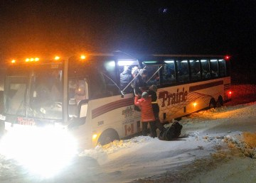 A bus lies ditched in snow outside Yellowknife as Arctic Winter Games athletes exit through the emergency escape - Sarah Pruys