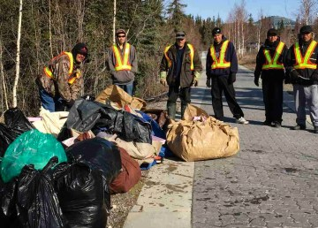 Workers in Yellowknife's Common Ground program pose with bags of garbage collected from the city's streets and trails