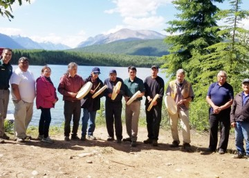 A group of Dehcho First Nations Elders, Parks Canada staff, and drummers pose for a photo to commemorate ceremony returning to the land in Nahanni National Park Reserve.