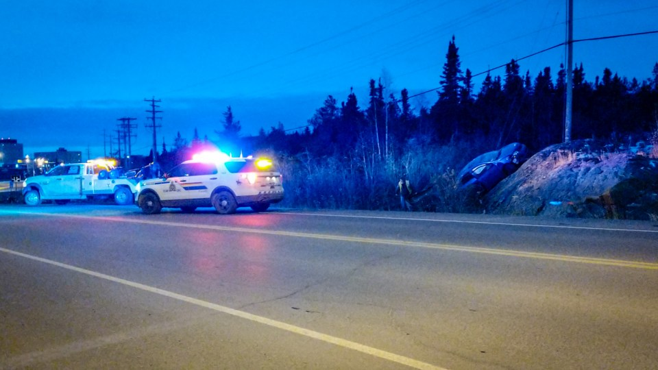 A recovery vehicle and RCMP SUV wait beside a beached vehicle on a highway leading into Yellowknife on October 4, 2018