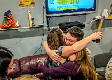 Rebecca Alty hugs Niels Konge beneath a screen showing municipal election results on election night 2018