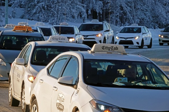 An Aurora Taxi cab driver joins City Cab colleagues in Monday's parade