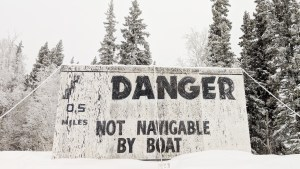 A file photo of a sign warning of the Cassette Rapids outside of Fort Fitzgerald in January 2019. Sarah Pruys/Cabin Radio