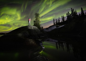 A visitor watches the northern lights from Yellowknife's Back Bay - James MacKenzie Photo-NWT Tourism