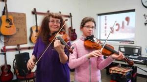 Linda Duford teaches Iga Olesinska the fiddle at the Purple Pick Studio. Sarah Pruys/Cabin Radio
