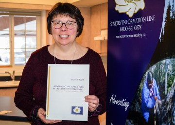 Suzette Montreuil, executive director of the NWT Seniors' Society, with a copy of the society's report studying living income for seniors