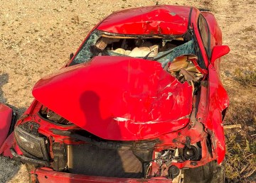 A badly damaged red car lies abandoned on an NWT highway