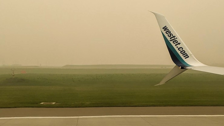 Wildfire smoke settles over Calgary Airport on Friday, as seen from an arriving WestJet flight