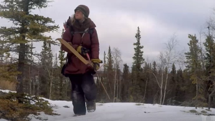 A contestant with a bow and arrow in the NWT wilderness during season six of Alone