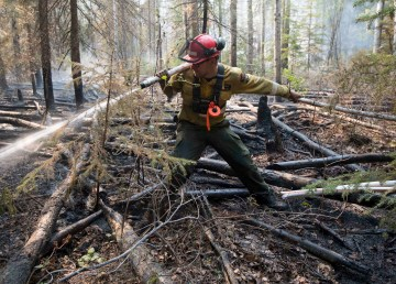 An Alberta firefighter works on the edge of a wildfire near High Level in May 2019
