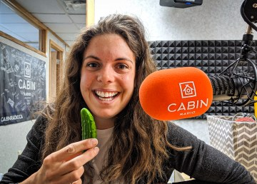 Yellowknife farmers' market manager Julie Downes with the first cucumber of the 2019 season inside Cabin Radio's Studio Two