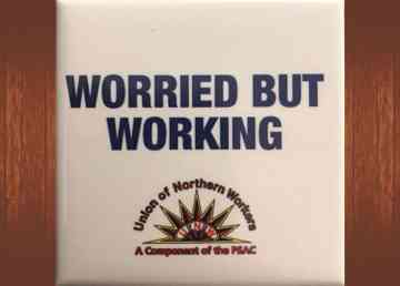 A UNW pin bearing the text 'worried but working'