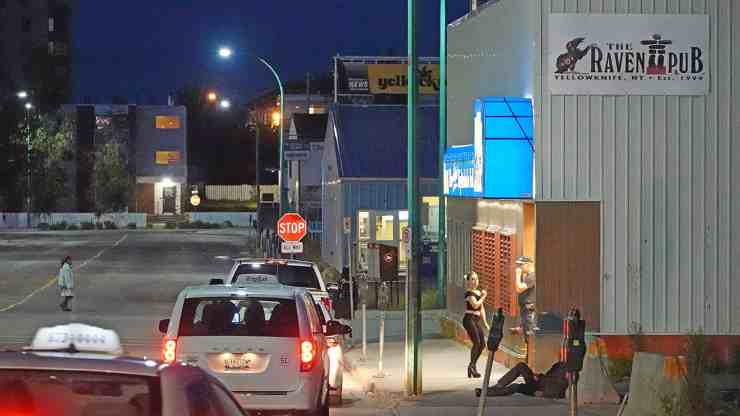 Taxi cabs wait for fares outside of The Raven Pub on a Saturday night