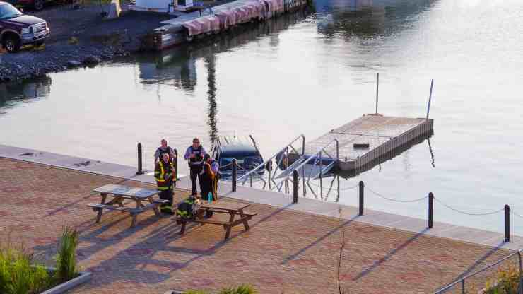 Emergency responders gather next to a partly submerged vehicle in Yellowknife's Old Town