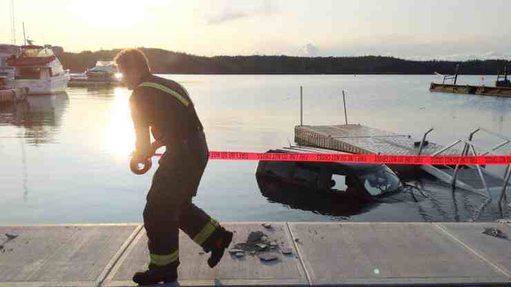 A firefighter tapes off the dock next to the submerged vehicle