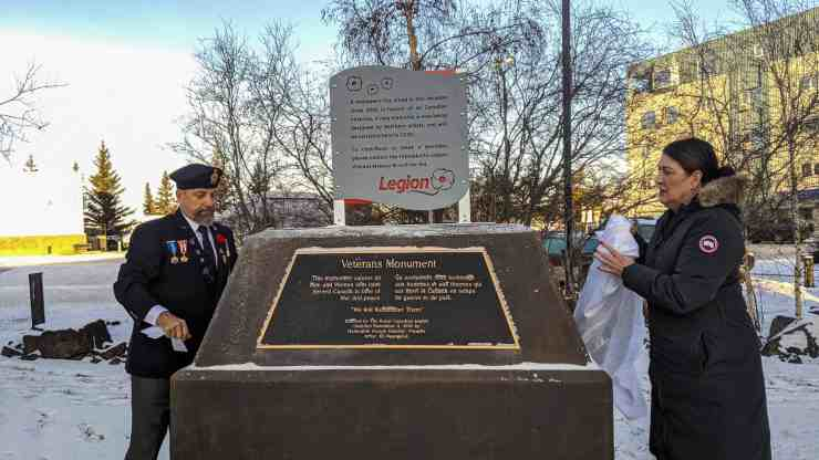 Legion members unveil a placeholder after a monument to veterans was vandalized