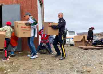 In a photo supplied by RCMP, an officer is seen helping to carry equipment into an Ulukhaktok storage room