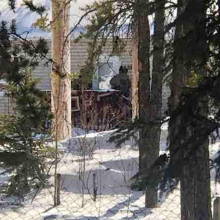 RCMP officers in tactical apparel outside a house in Fort Smith on March 31, 2020