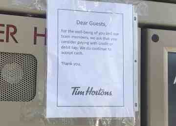 A sign at the Tim Hortons drive-through on Old Airport Road in Yellowknife asks customers to pay by debit or credit tap