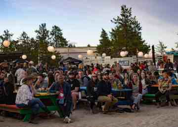 Folk on the Rocks attendees watch an act perform at the beer garden stage in 2019. Sarah Pruys/Cabin Radio